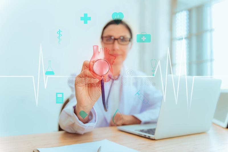 Female Doctor is Holding Stethoscope for Heart Model Check Up in Laboratory, Close Up of Scientist Practitioner Analyzing Health. Female Medical Doctor is royalty free stock image