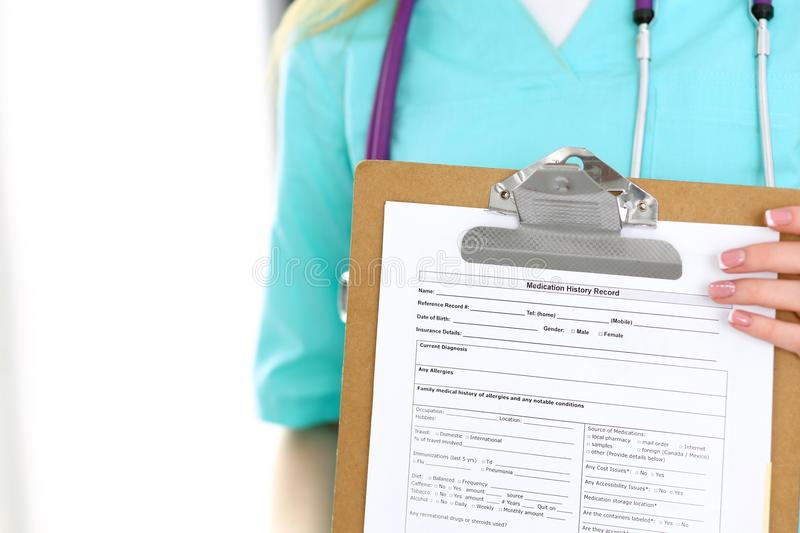 Female doctor holds medication history form while standing straight in hospital closeup. Healthcare, insurance and royalty free stock photos