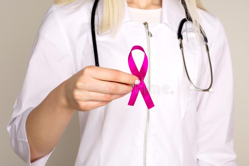 Female Doctor Holds Pink Ribbon, International Breast Cancer Day October 7. Image royalty free stock images