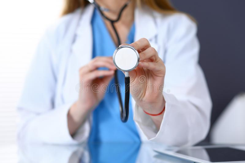 Female doctor holds stethoscope head, just hands closeup. Physician ready to examine and help patient. Medical help and stock image
