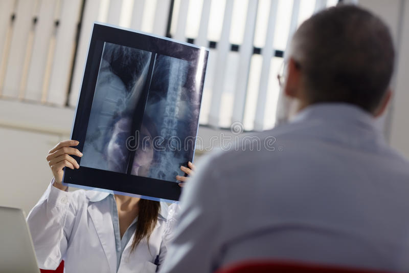 Female doctor in hospital with patient and x-rays stock image