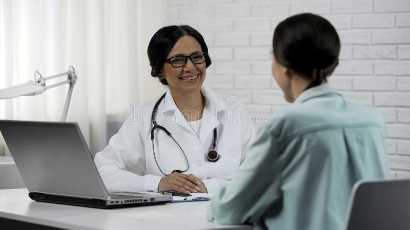 Female doctor informing good results to patient, promising to help, healthcare royalty free stock photography