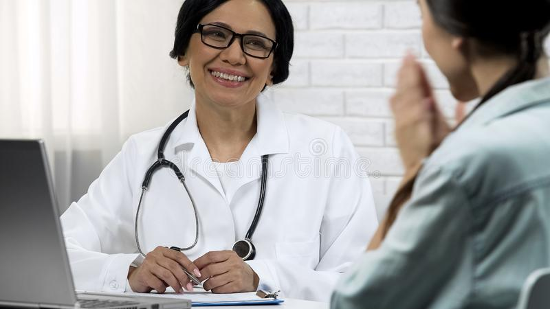 Female doctor informing patient about recovery, good results of treatment royalty free stock photo