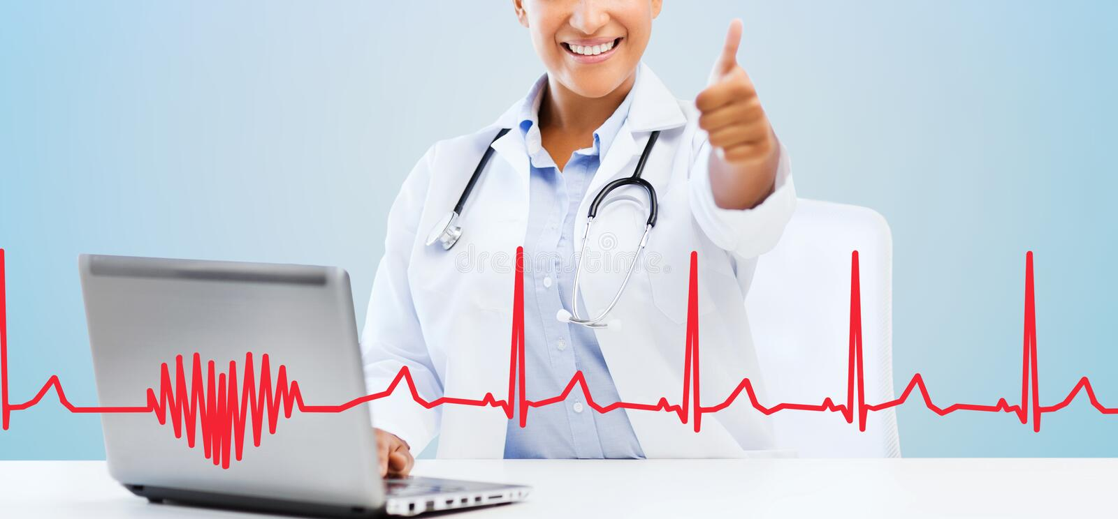 Female doctor with laptop pc showing thumbs up. Healthcare, medical and technology concept - happy african american female doctor with laptop pc computer showing stock images