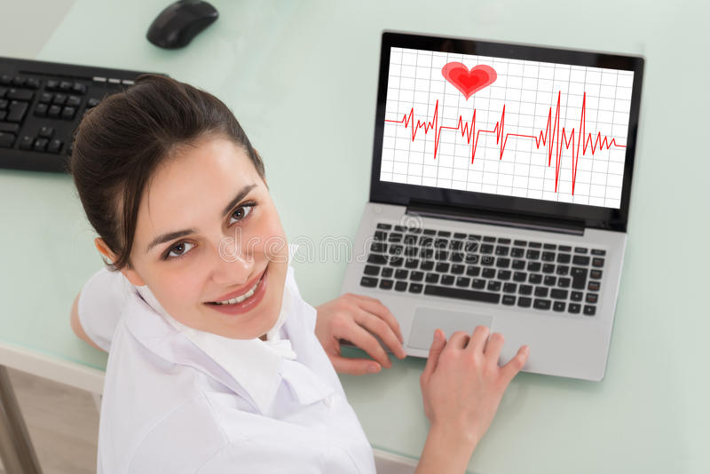 Female Doctor With Laptop Showing Heartbeat. Happy Young Female Doctor With Laptop Showing Heartbeat royalty free stock images