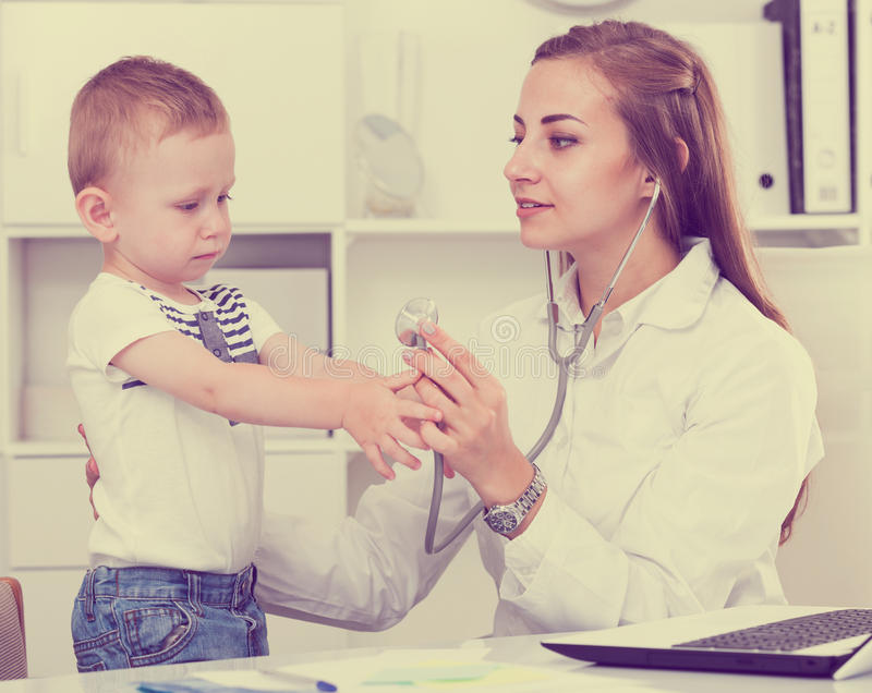 Female doctor is listening child with a stethoscope royalty free stock images