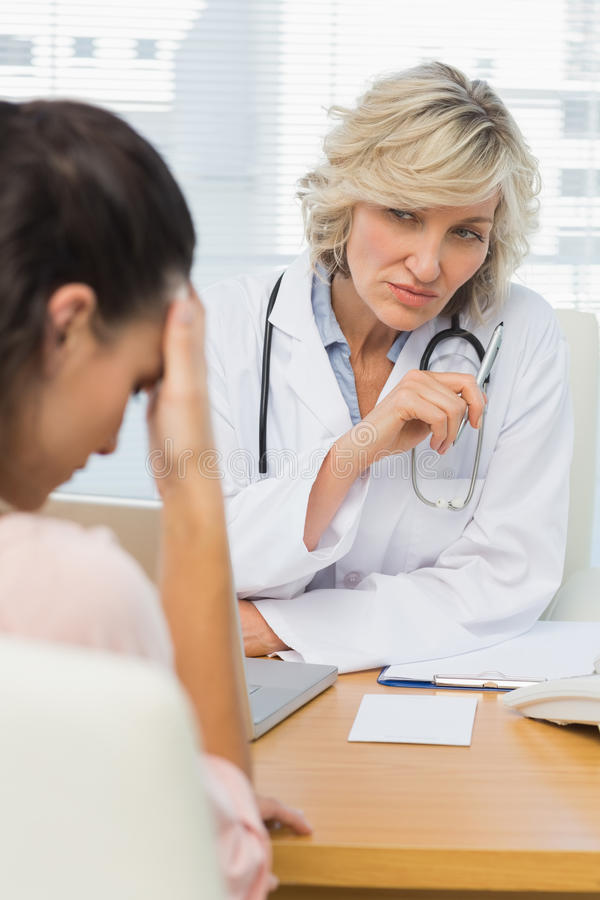 Female doctor listening to patient with concentration. At desk in medical office stock photography