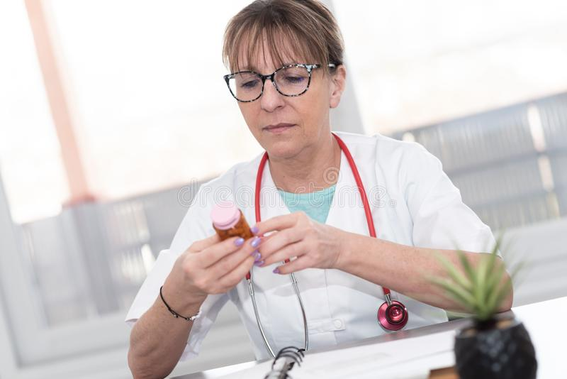 Female doctor looking at a bottle of pills. In medical office royalty free stock photography