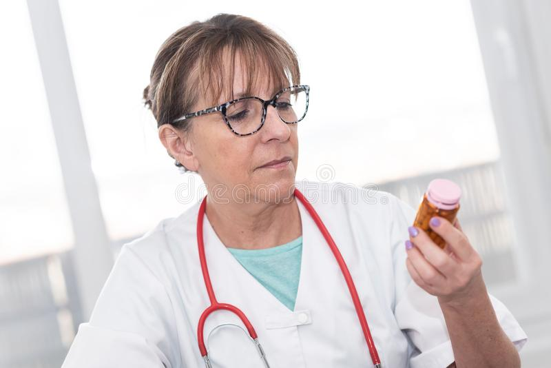 Female doctor looking at a bottle of pills. In medical office royalty free stock images