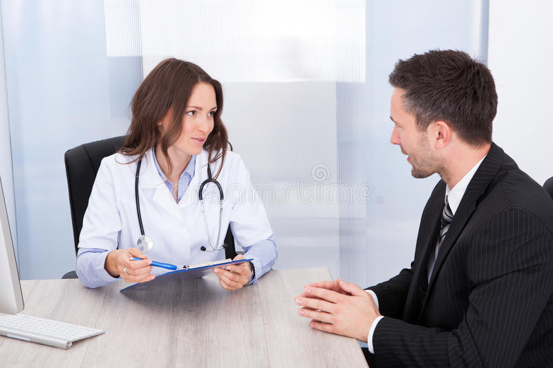 Female doctor looking at businessman. Young Female Doctor Holding Clipboard Talking With Businessman royalty free stock photo
