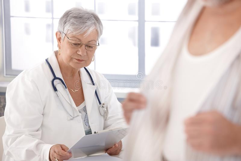 Female doctor looking at papers. Senior female doctor looking at papers, sitting at desk royalty free stock images