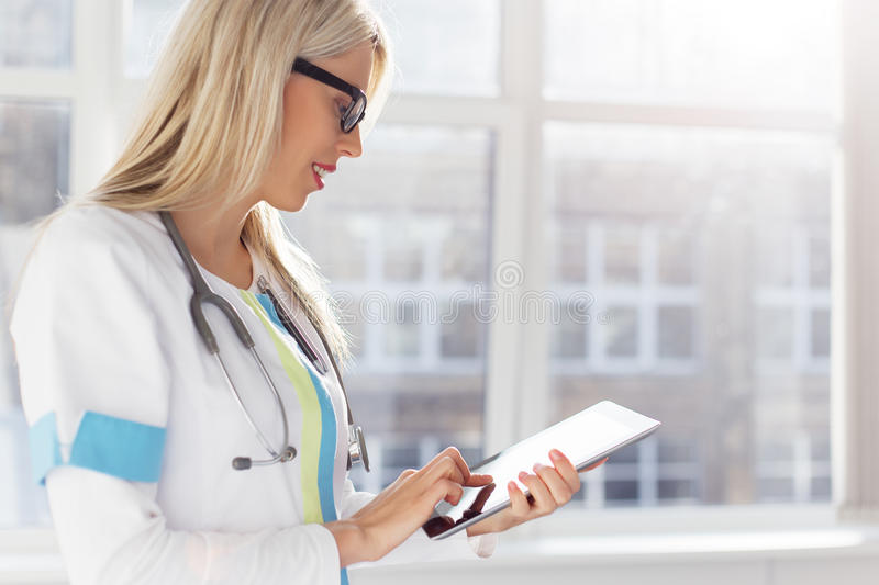 Female doctor looking on tablet computer. Female doctor looking at medical records on tablet computer stock image