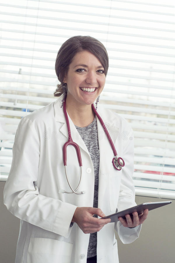 Female doctor looking at tablet for medical information stock photos