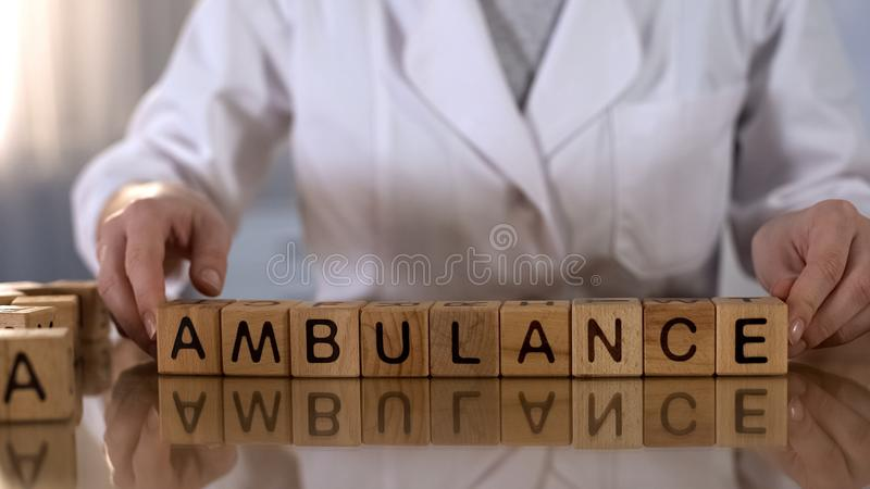 Female doctor making word ambulance of wooden cubes, urgent medical service. Stock photo stock photography