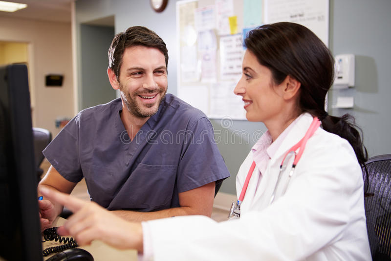 Female Doctor With Male Nurse Working At Nurses Station. Looking At Each Other Smiling royalty free stock photo
