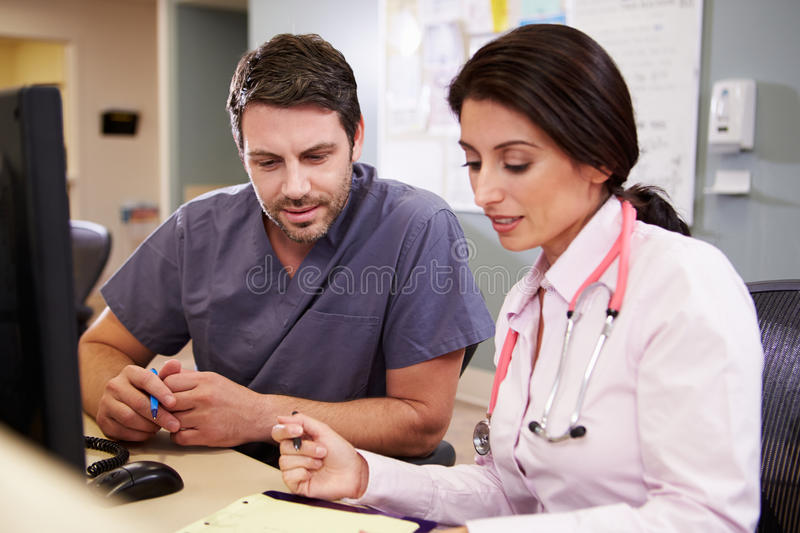 Female Doctor With Male Nurse Working At Nurses Station. Looking At Notes Talking royalty free stock photos