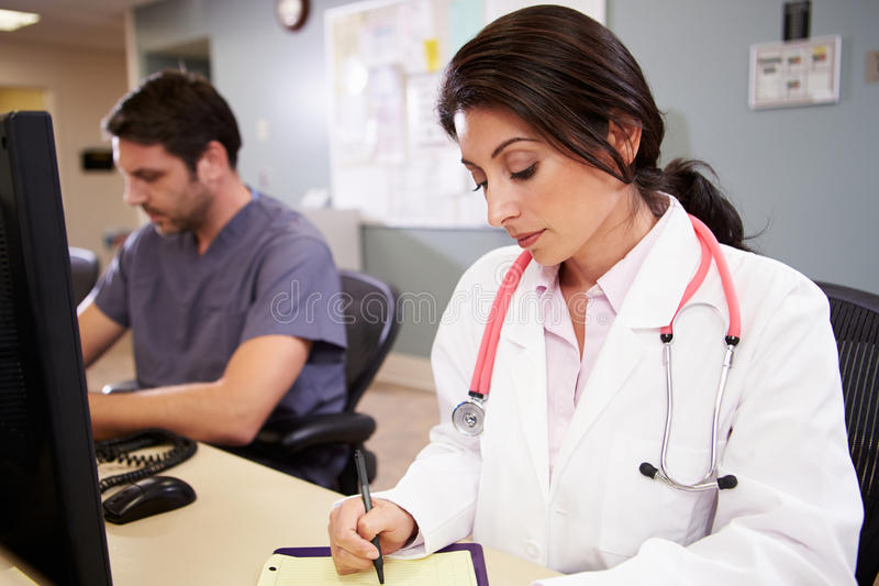 Female Doctor With Male Nurse Working At Nurses Station Stock Photo - Image 35799750-8180