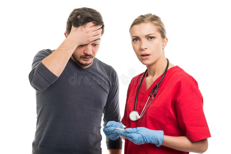 Female doctor and male patient looking surprised about high fever. stock photography