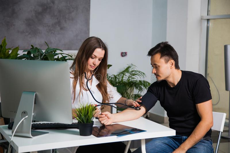 Female doctor measuring arterial blood pressure for patient at clinic stock photos