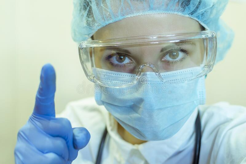 A female doctor in a medical mask, glasses, and gloves sternly hold up her index finger, a sign of advice to be careful. A female doctor in a medical mask royalty free stock images