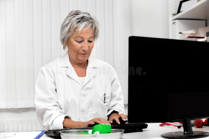 Female doctor in the medical office, concept telemedicine, e-health and computer royalty free stock photos