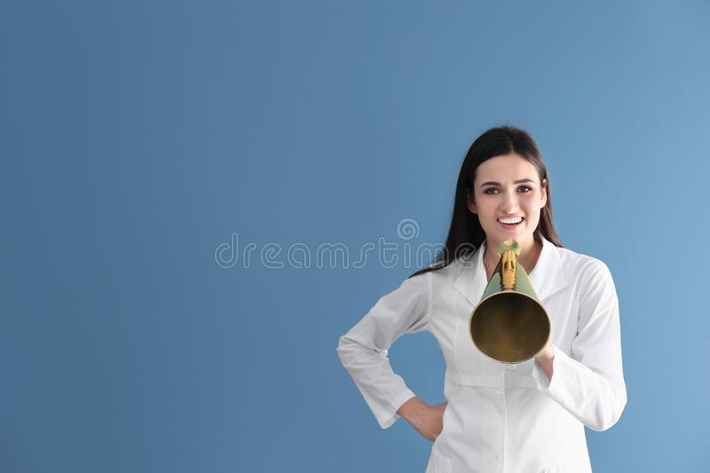 Female doctor with megaphone. On color background stock photo