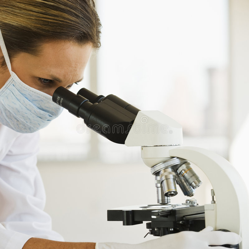 Female Doctor with Microscope. Female Doctor with mask looking through Microscope in lab stock photography