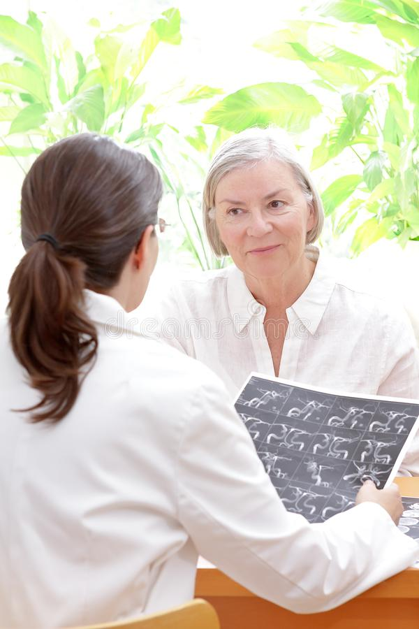 Doctor patient mri blood vessels. Female doctor with an mra image or angiogram discussing with a senior patient her risk to suffer an apoplectic stroke, copy stock images
