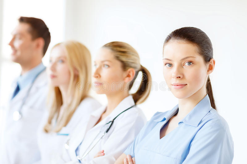 Female doctor or nurse in front of medical group stock photo
