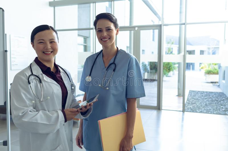 Female doctor and nurse looking at camera in the lobby at hospital. Front view of happy diverse female doctor and female Caucasian nurse looking at camera in the royalty free stock photos
