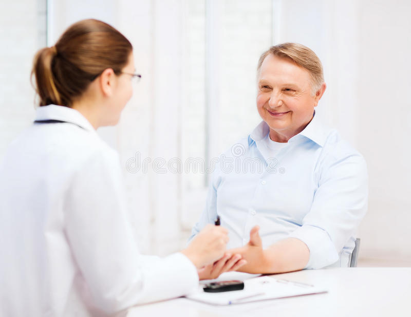 Female doctor or nurse measuring blood sugar value stock images