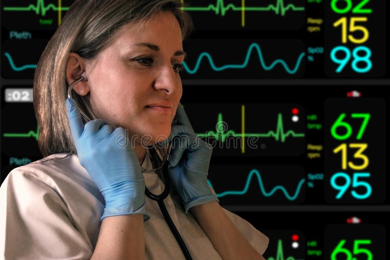 Female doctor or nurse puts in stethoscope in ears. Electrocardiogram screen monitor softly blurred on background. Woman wears. Uniform and blue latex gloves stock photo