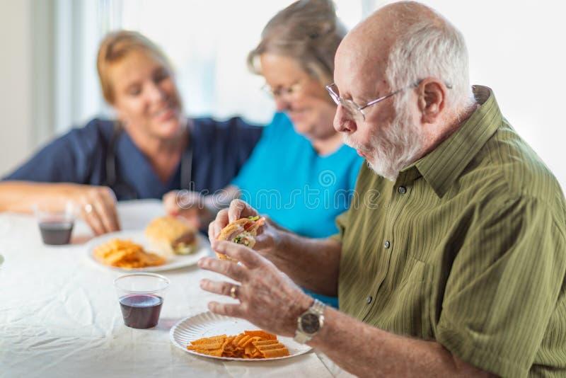 Female Doctor or Nurse Serving Senior Adult Couple Sandwiches stock photo