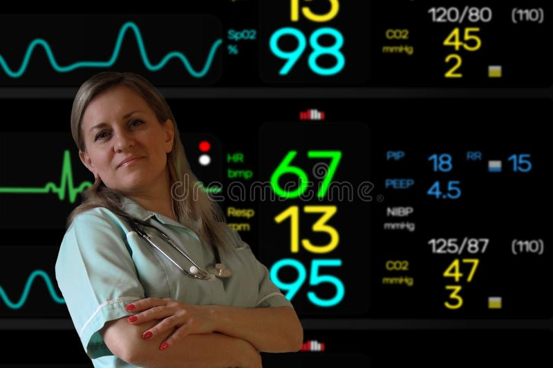 Female doctor or nurse stay in uniform with stethoscope and looks at camera smiling. Electrocardiogram screen monitor softly. Blurred on background royalty free stock photography