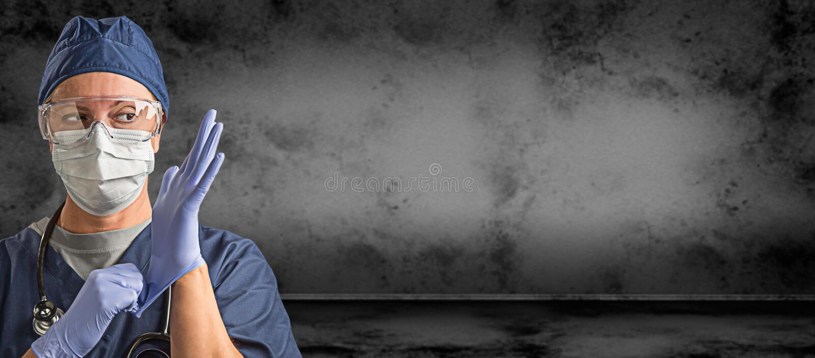 Female Doctor or Nurse Wearing Goggles, Surgical Gloves and Face Mask Against Grungy Dark Background Banner stock images