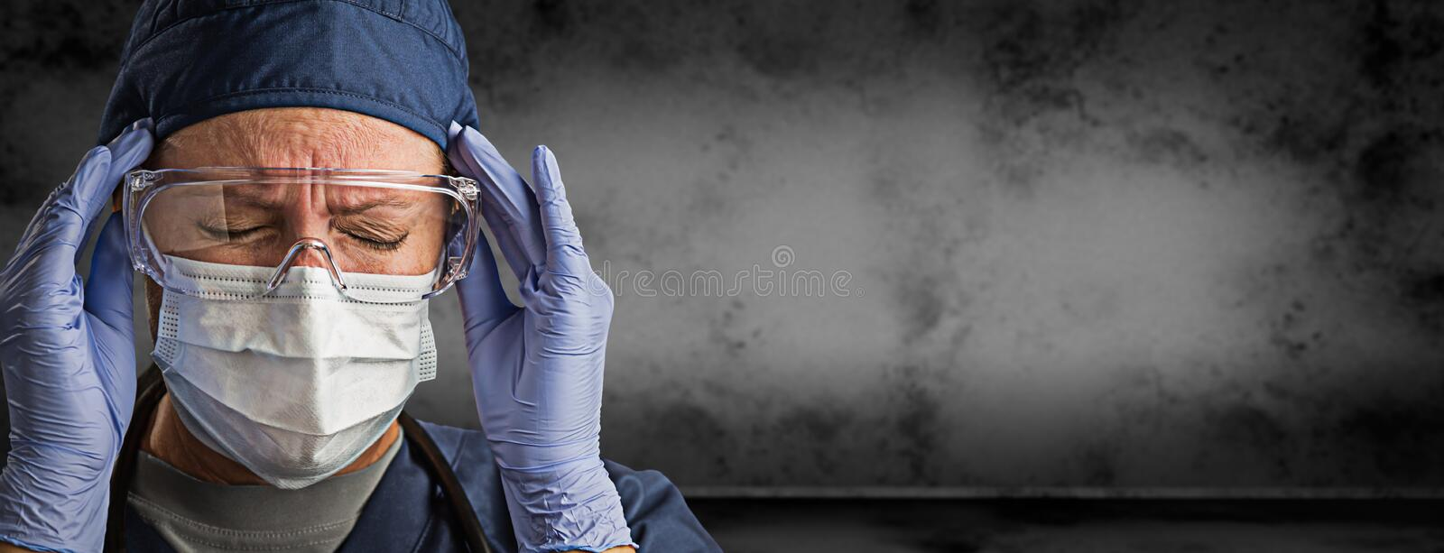 Female Doctor or Nurse Wearing Goggles, Surgical Gloves and Face Mask Against Grungy Dark Background Banner royalty free stock images