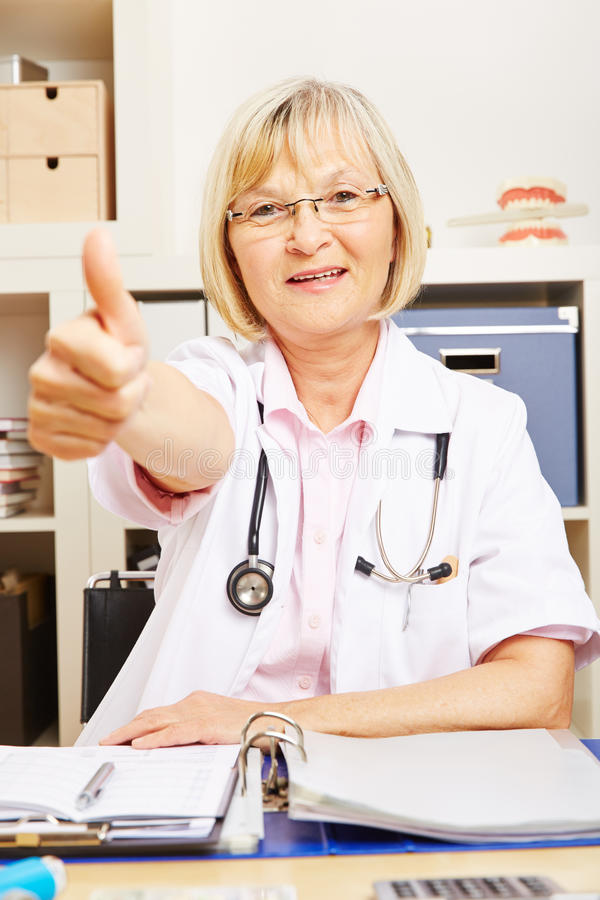 Female doctor in office holding thumbs up stock image