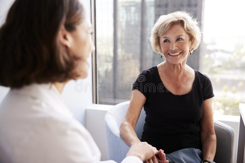 Female Doctor In Office Reassuring Senior Woman Patient And Holding Her Hands royalty free stock images