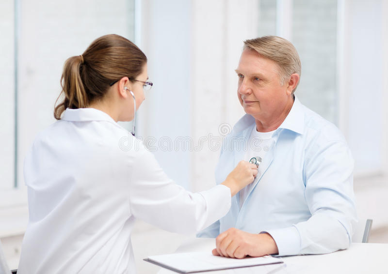 Female doctor with old man listening to heart beat stock photos