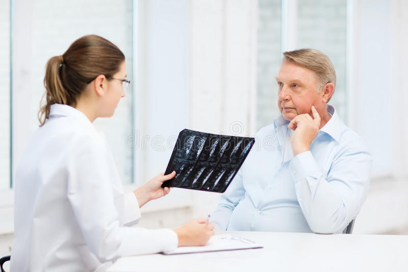 Female doctor with old man looking at x-ray stock photo