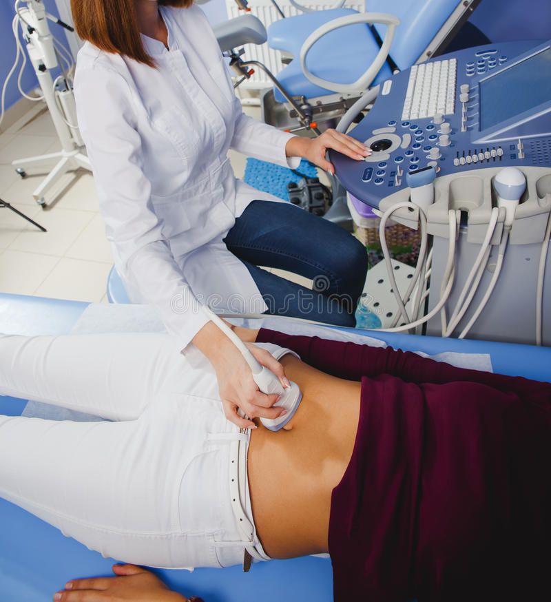 Female doctor operating ultrasound scanner. Examining belly of her female patient stock photos