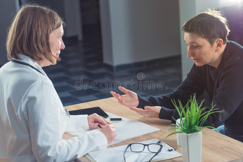 Female doctor and patient consultation during medical exam stock photography