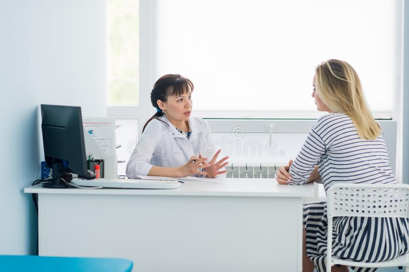 Female doctor and patient talking in hospital office. Health care and client service in medicine royalty free stock photo