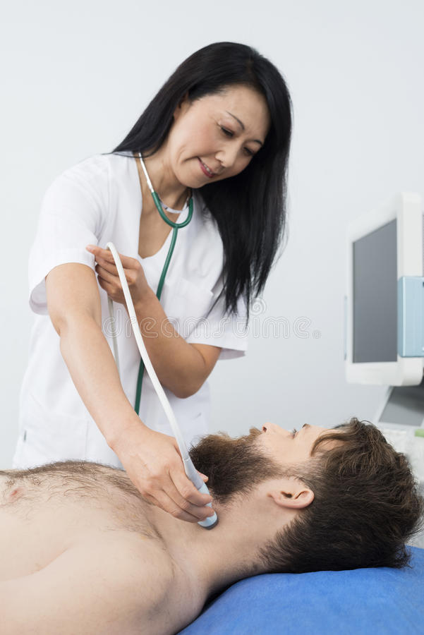 Female Doctor Performing Thyroid Ultrasound Test On Male Patient. Mature female doctor performing thyroid ultrasound test on male patient in hospital stock photos