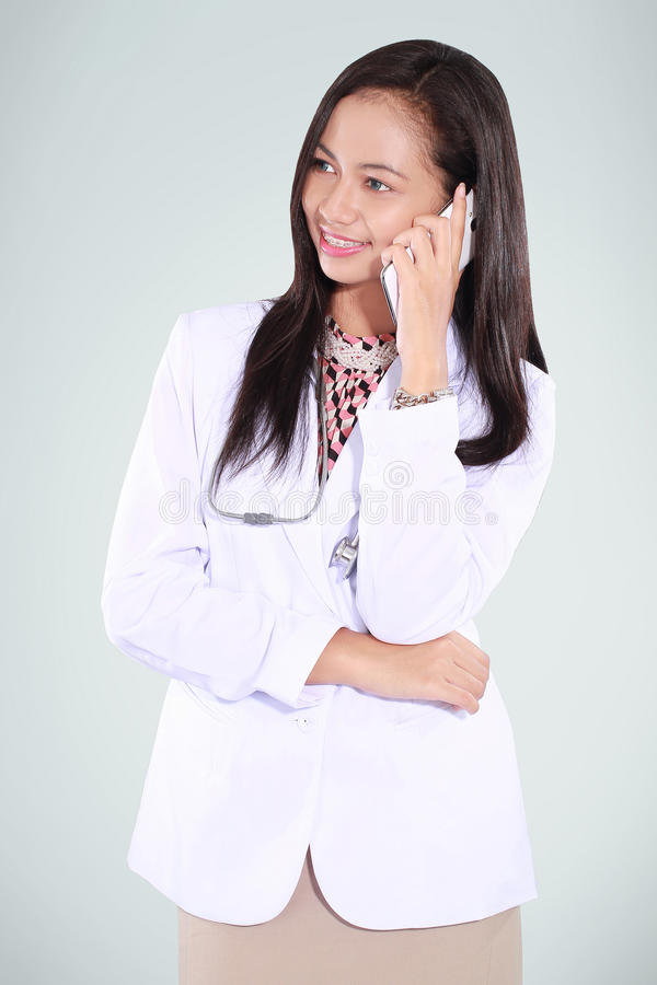 Female doctor on the phone. Isolated on green background royalty free stock image