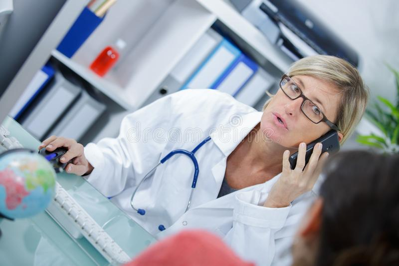 Female doctor on phone at office. Female stock images