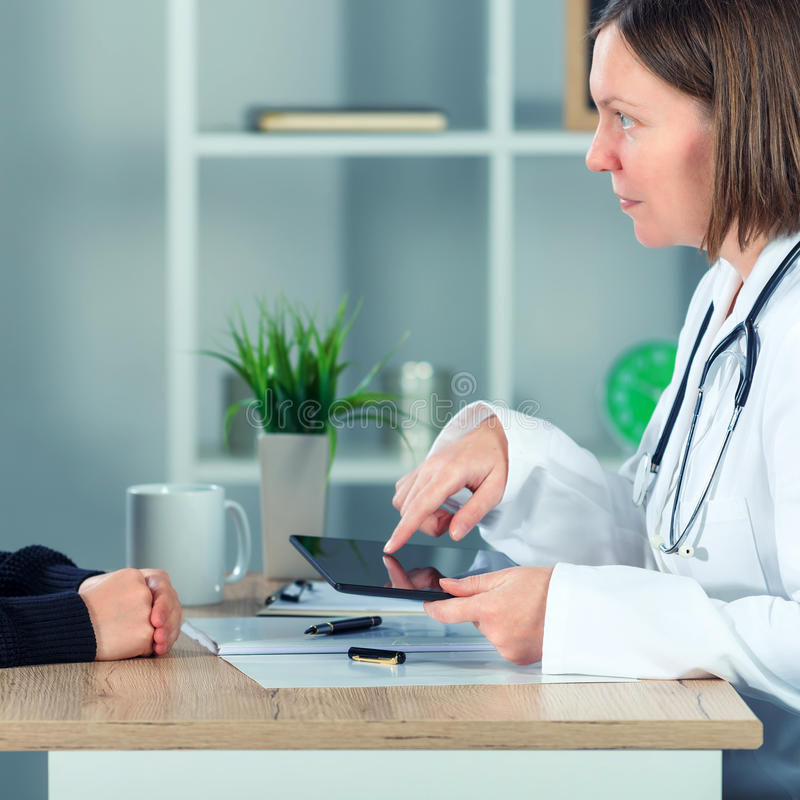 Female doctor presenting medical exam results to patient using t royalty free stock photography