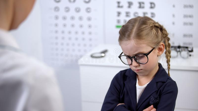 Female doctor putting glasses on disgruntled girl, child feels insecure, upset. Stock photo stock photography