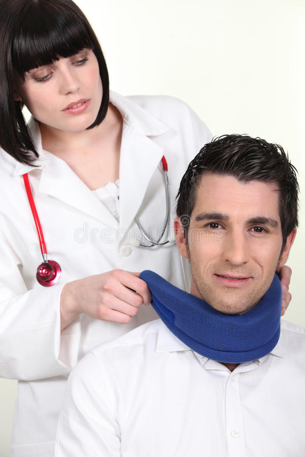 Female doctor putting neck brace to a patient stock photo