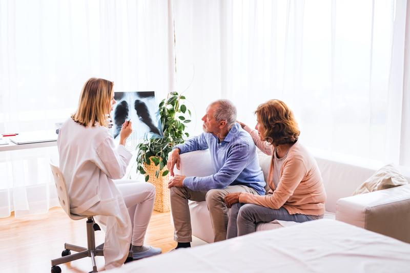 Female doctor with x-ray talking to a senior couple. Female doctor with x-ray talking to a senior couple at the office royalty free stock images